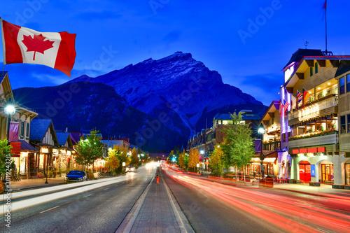 Fotografie, Obraz Canadian flag with Banff Avenue at twilight time, Alberta, Canada