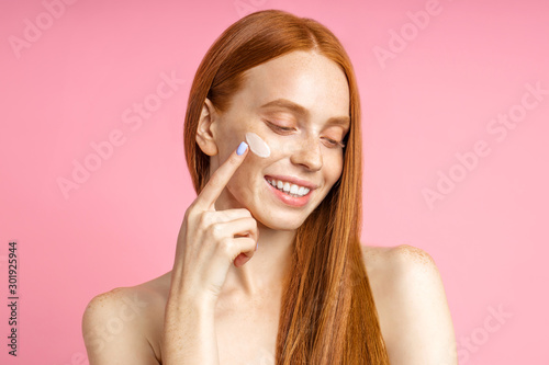 Valokuva  Beautiful young ginger woman with cream on face
