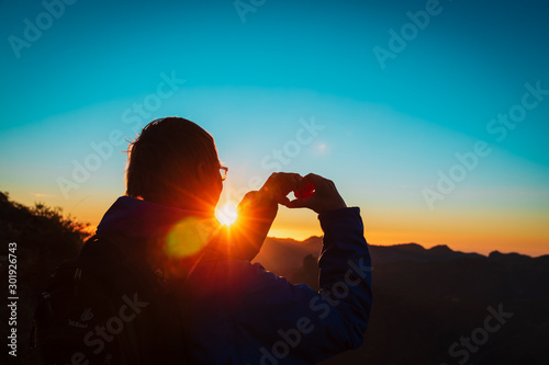 Garden Poster Coral tourist enjoy sunset in mountains, making heart with hands