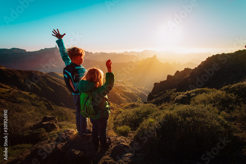 Obraz happy boy and girl travel in mountains at sunset - fototapety do salonu
