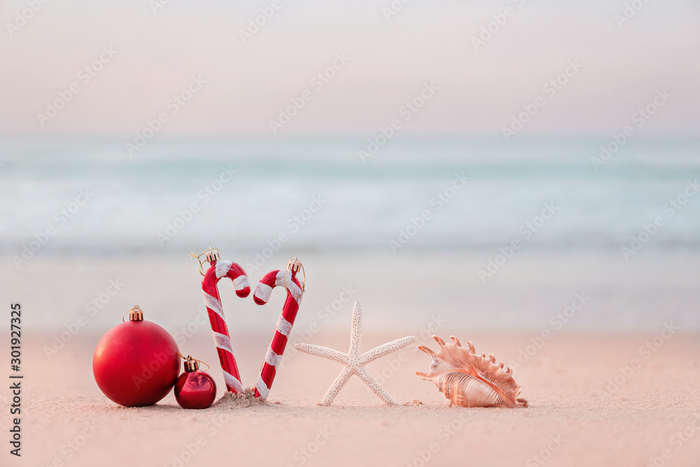 Fototapety, obrazy: Christmas ball and starfish on yellow sand and sea background. New Yeaar or Xmas holiday vacation in exotic countries or tropics concept: christmas decorations on the beach. Copy space for text