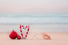 Christmas Ball And Starfish On Yellow Sand And Sea Background. New Yeaar Or Xmas Holiday Vacation In Exotic Countries Or Tropics Concept: Christmas Decorations On The Beach. Copy Space For Text