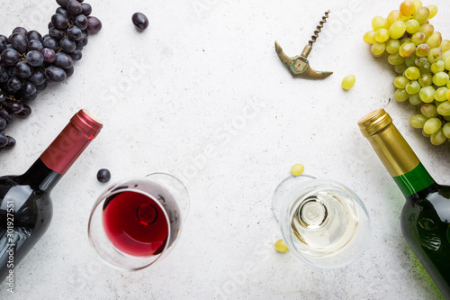 Fotografía  Glasses of white and red wine with ripe grapes on stone background, top view