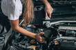 Beautiful Mechanic girl in a black jumpsuit and a white T-shirt changes the oil in a black car.close up photo. car repair concept