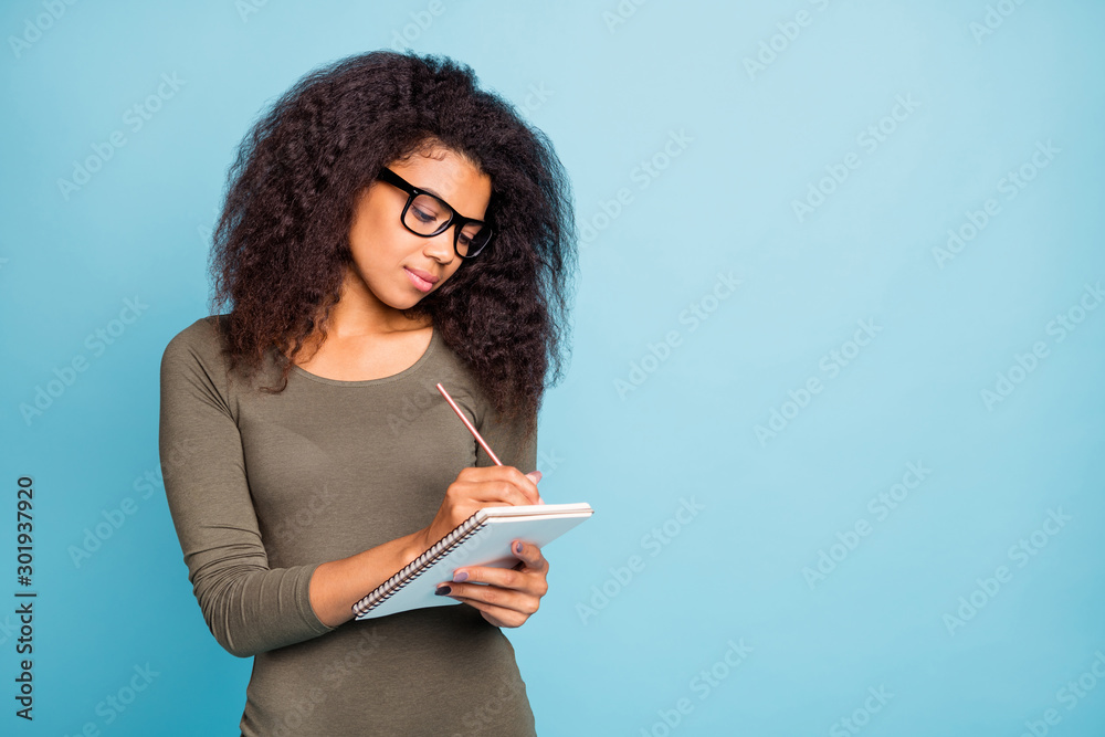 Fototapeta Portrait of concentrated mulatto girl write in copybook prepare project wear spectacles modern shirt isolated over blue color background