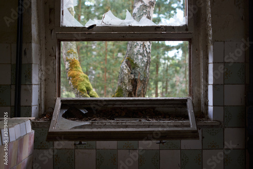 Photo  Broken window looking into the wilderness at communist abandoned soviet military