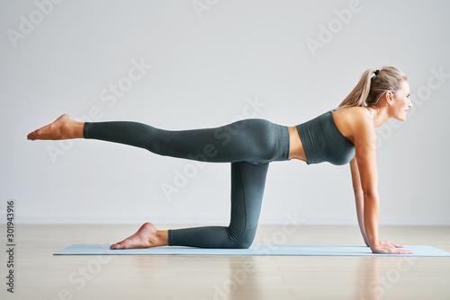 Fototapeta Adult woman practising yoga at home