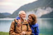 canvas print picture - Senior pensioner couple hiking by lake in nature, resting.