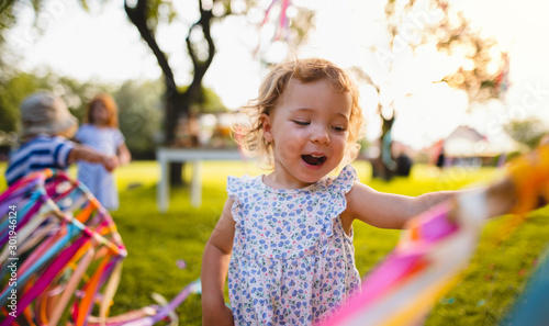 A front view of small girl on birthday party outdoors in garden in summer Wallpaper Mural