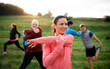 canvas print picture Large group of fit and active people stretching after doing exercise in nature.