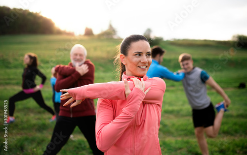 Obraz Large group of fit and active people stretching after doing exercise in nature. - fototapety do salonu