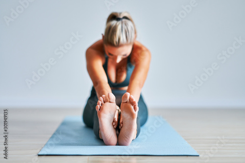 Foto auf Leinwand Yoga schule Adult woman practising yoga at home