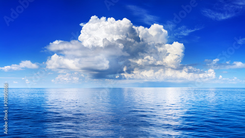Fotobehang Donkerblauw White cumulus clouds in blue sky over sea landscape, big cloud above ocean water panorama, horizon, beautiful tropical sunny summer day seascape panoramic view, cloudy weather, cloudscape, copy space