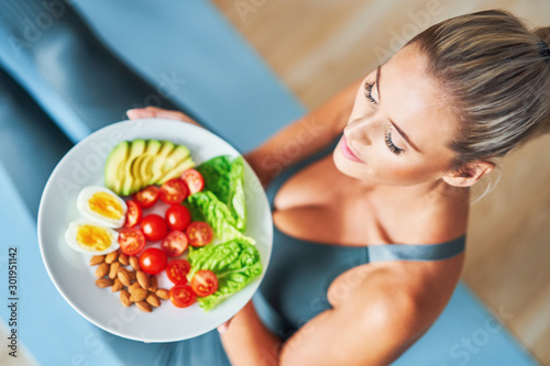 Fotografiet Adult woman eating healthy lunch and sitting on yoga mat
