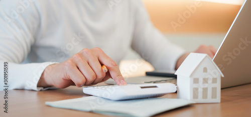 Fotografering close up young man hand press on calculator to check and summary expense of home