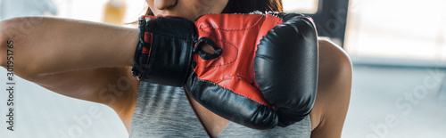 Obraz panoramic shot of sportswoman in boxing glove in sports center - fototapety do salonu