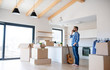 canvas print picture - Mature man with boxes moving in new house, using smartphone.