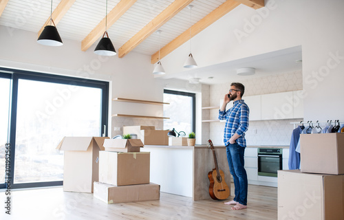 Obraz Mature man with boxes moving in new house, using smartphone. - fototapety do salonu
