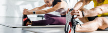 Panoramic Shot Of Sportsman And Sportswoman Stretching On Fitness Mats In Sports Center