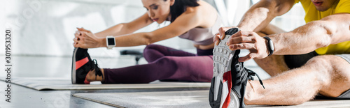 Fotografia panoramic shot of sportsman and sportswoman stretching on fitness mats in sports