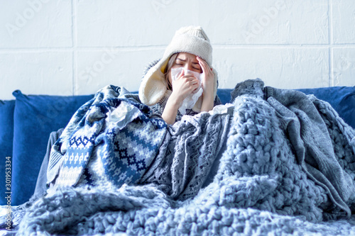Sick exhausted girl in white warm hat wrapped herself in scarves and blankets is sitting in bed Fototapet