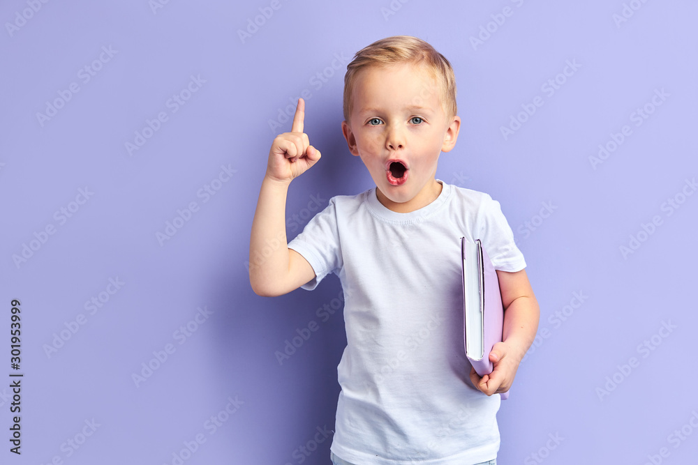 Fototapety, obrazy: Caucasian child show bright emotions standing over purple background, holding purple notebook. With opened mouth