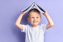 Portrait Of Joyful Caucasian Child In Casual Clothes After Education, After Reading Wants To Play. Funny Boy Holding Book Above His Head
