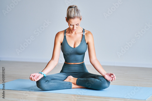 Obraz Adult woman practising yoga at home - fototapety do salonu