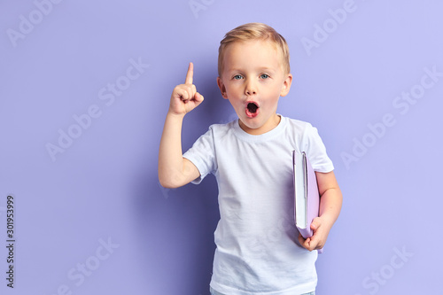 Fototapeta Caucasian child show bright emotions standing over purple background, holding purple notebook. With opened mouth obraz