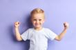 Leinwandbild Motiv Winner kid isolated over purple background, show how powerful he is. Isolated over purple background