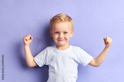 Cuadros en Lienzo  Winner kid isolated over purple background, show how powerful he is