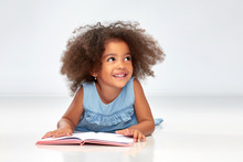 Childhood, School And Education Concept - Happy Smiling Little African American Girl Reading Book Over Grey Background