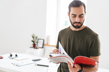 Image Of Caucasian Serious Man Holding And Reading Brochure