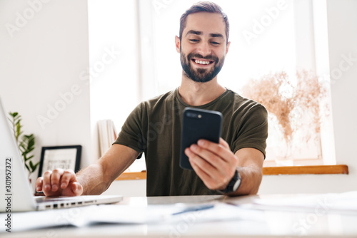 Fotografía Image of handsome happy man typing on laptop and using cellphone