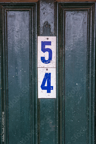 Fotografia  The number 54 is attached to a green pitted wooden door