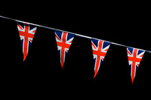 Backlit Union Jack Flag Bunting Hanging In Bright Sun Across A Dark, Distant Background