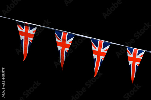 Photo Backlit Union Jack flag bunting hanging in bright sun across a dark, distant bac