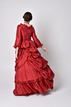 Full Length Portrait Of A Brunette Girl Wearing A Red Silk Victorian Gown. Standing Pose, With Back To The Camera,  On A White Studio Background.
