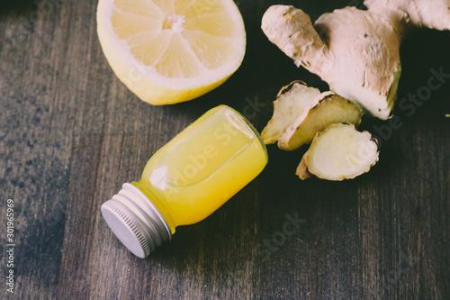 Fototapeta Healthy Ginger lemon shots in small glass bottles on wooden background obraz