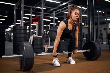 Young pretty fitness lady trying to lift heavy barbell from brown floor in modern gym hal, looking away with concentrated face, training hard for competition, indoor shot