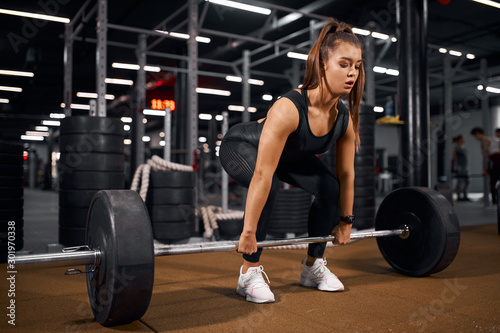 plakat Young pretty fitness lady trying to lift heavy barbell from brown floor in modern gym hal, looking away with concentrated face, training hard for competition, indoor shot