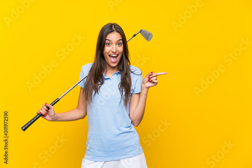 Young golfer woman over isolated yellow wall surprised and pointing finger to th Fototapeta