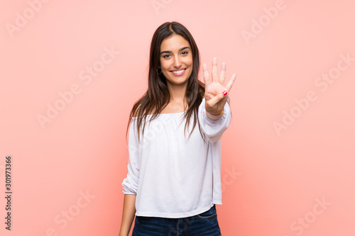 Fotografering Young woman over isolated pink background happy and counting four with fingers