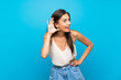 Young woman over isolated blue background listening to something by putting hand on the ear