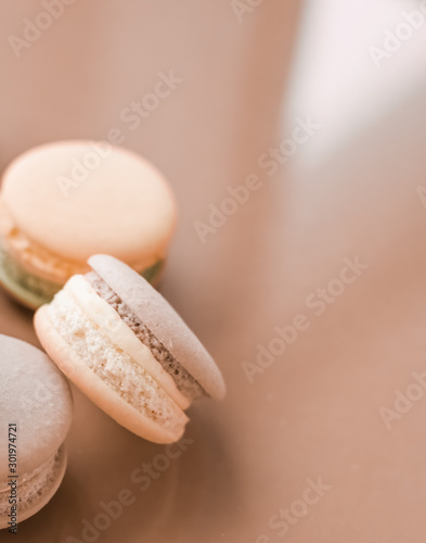 Photographie  French macaroons on cream beige background, parisian chic cafe dessert, sweet fo