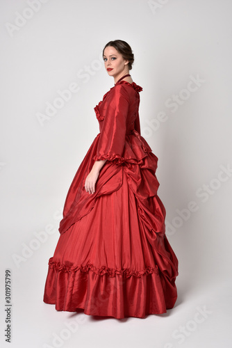 Obraz full length portrait of a brunette girl wearing a red silk victorian gown. Standing in side profile on a white studio background. - fototapety do salonu