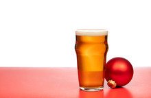 Pint Glass Of Ale Or Beer With Christmas Bauble On Red Background