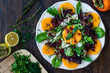 Persimmon Fruit Salad with Pomegranate, Lollo Rosso Lettuce, Rocket Arugula or Rucola and Mint Leaves.