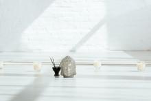 Decorative Buddha Head Near Aromatic Sticks And Candles On White Floor
