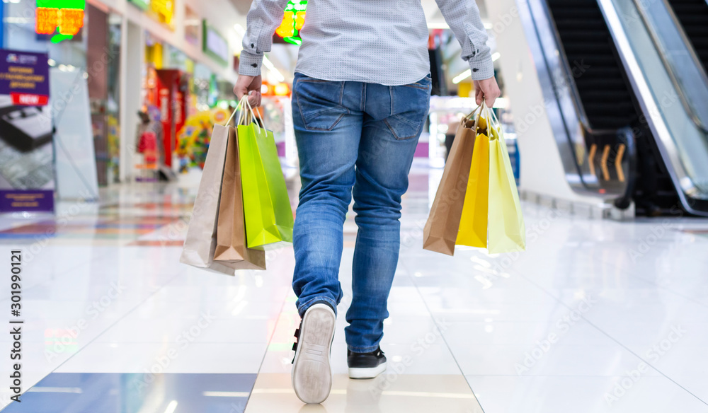 Fototapety, obrazy: Shopping concept. Guy walking in shopping mall, back view